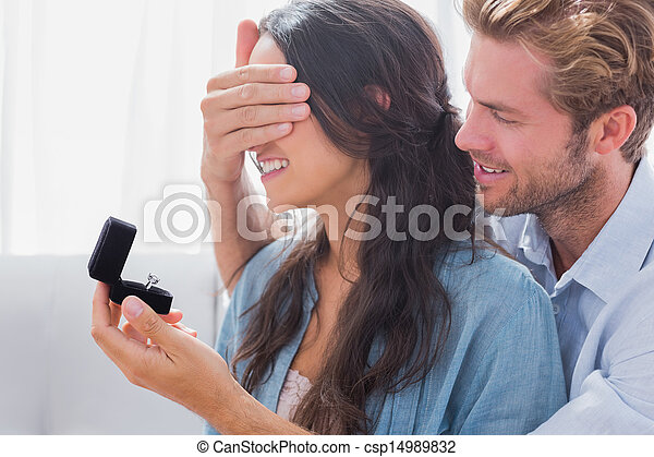Un hombre escondiendo los ojos de su esposa para ofrecerle un anillo de compromiso - csp14989832
