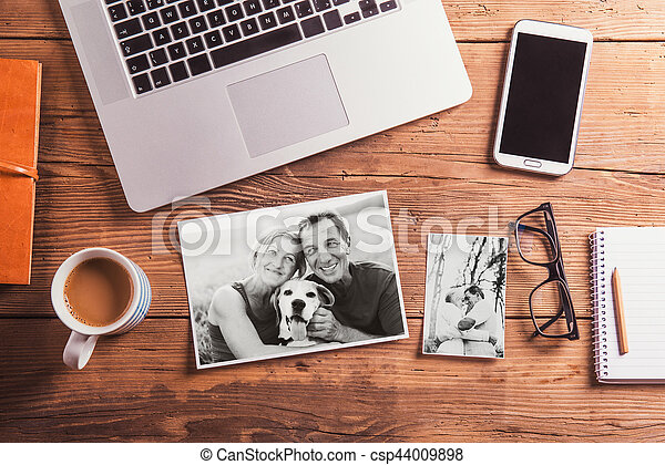 Office desk. Objects and black-and-white photos of senior couple - csp44009898