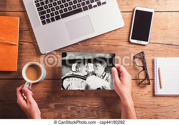 Office desk. Objects and black-and-white photo of senior couple - csp44180292