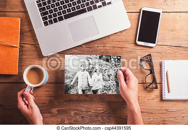 Office desk. Objects and black-and-white photo of senior couple - csp44391595