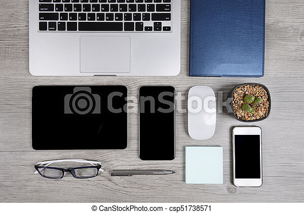 Office table with laptop computer, notebook, digital tablet, pen, smartphone, mouse, eyeglasses and coffee on white wood background. Desktop office mockup concept. - csp51738571