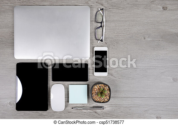 Office table with laptop computer, digital tablet, pen, smartphone, mouse, eyeglasses and coffee on white wood background. Desktop office mockup concept. - csp51738577