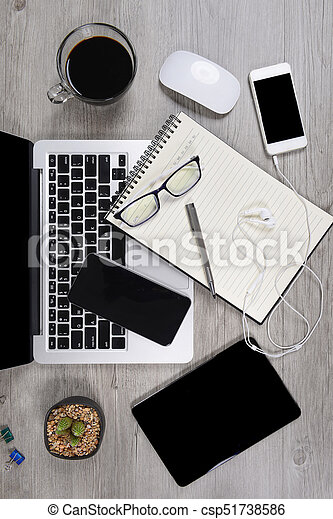 Office table with laptop computer, notebook, digital tablet, pen, smartphone, mouse, eyeglasses and coffee on white wood background. Desktop office mockup concept. - csp51738586