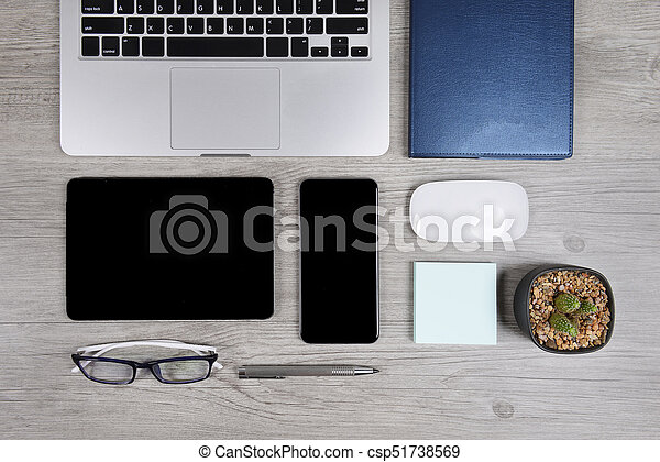 Office table with laptop computer, notebook, digital tablet, pen, smartphone, mouse, eyeglasses and coffee on white wood background. Desktop office mockup concept. - csp51738569