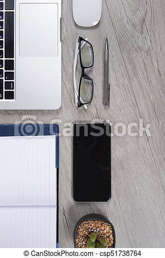 Office table with laptop computer, notebook, digital tablet, pen, smartphone, mouse, eyeglasses and coffee on white wood background. Desktop office mockup concept. - csp51738764