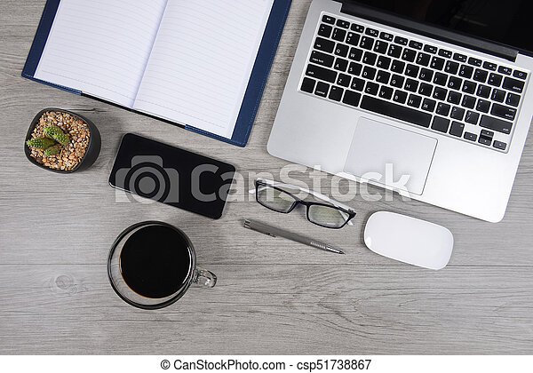 Office table with laptop computer, notebook, digital tablet, pen, smartphone, mouse, eyeglasses and coffee on white wood background. Desktop office mockup concept. - csp51738867