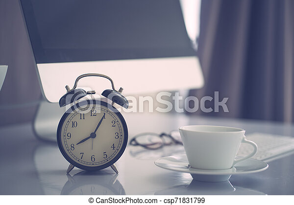 Office work space computer desk with coffe and clock, vintage colored filltered - csp71831799