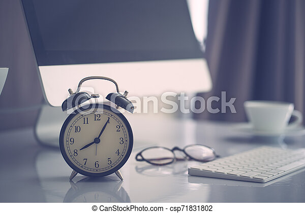 Office work space computer desk with coffe and clock, vintage colored filltered - csp71831802