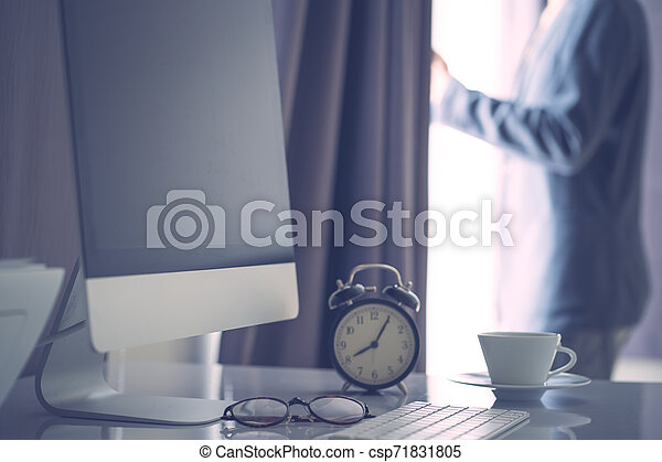 Office work space computer desk with coffe and clock, vintage colored filltered - csp71831805