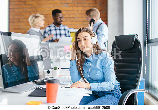 office worker in casual clothes with headphones on her head looking at camera - csp56912509