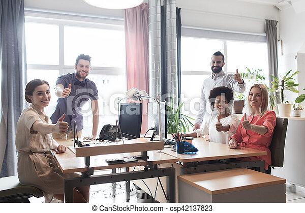 Feliz equipo creativo mostrando pulgares arriba en la oficina - csp42137823
