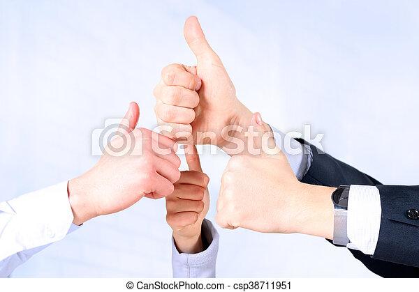 Feliz equipo de negocios mostrando pulgares arriba en la oficina - csp38711951