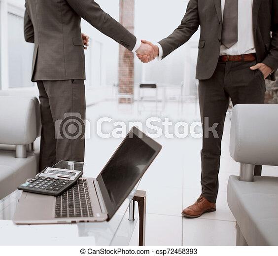 Laptop y calculadora en el escritorio de la oficina - csp72458393