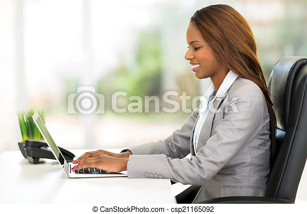 Trabajador de oficinas africano usando computadora portátil - csp21165092