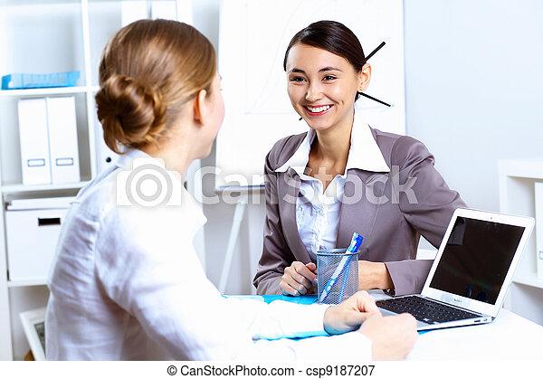 Las mujeres jóvenes de negocios trabajan en la oficina - csp9187207