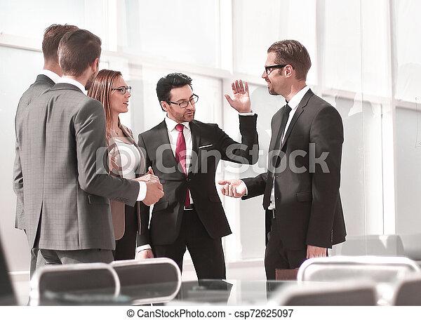 Empleados hablando parados en la oficina - csp72625097