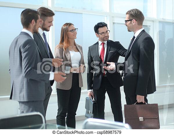 Empleados hablando parados en la oficina - csp58987579