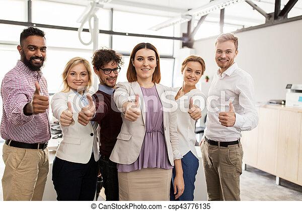 Feliz equipo de negocios mostrando pulgares arriba en la oficina - csp43776135