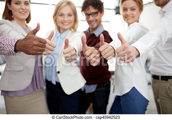 Feliz equipo de negocios mostrando pulgares arriba en la oficina - csp45942523