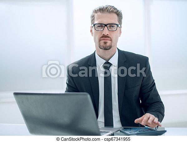 Hombre de negocios usando calculadora en el escritorio de la oficina con portátil - csp67341955