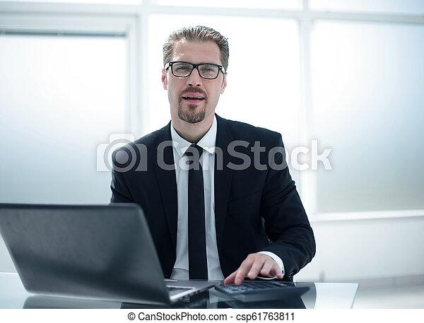 Hombre de negocios usando calculadora en el escritorio de la oficina con portátil - csp61763811