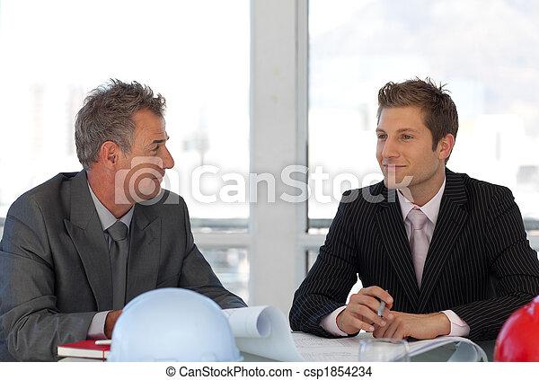Potrato de dos ingenieros holgazaneando en los planos de la oficina - csp1854234
