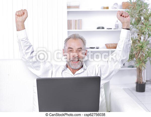 Un hombre de negocios feliz con portátil sentado en el sofá en la oficina - csp62756038