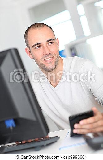 Trabajador de oficinas sonriente sentado frente a la computadora - csp9996661