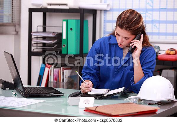 Mujer trabajadora de la construcción tomando una llamada en la oficina - csp8578832