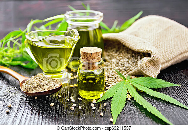 Oil hemp in two jars and sauceboat on wooden board - csp63211537