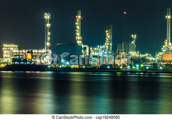 Oil refinery at night with shadow in river - csp19248085
