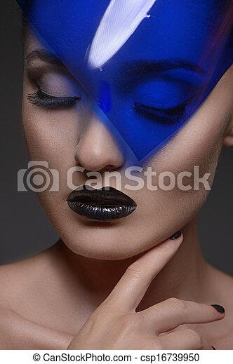 Luces misteriosamente. Retrato de mujeres hermosas con ojos cerrados sosteniendo la mano en la barbilla mientras están aislados en el gris - csp16739950