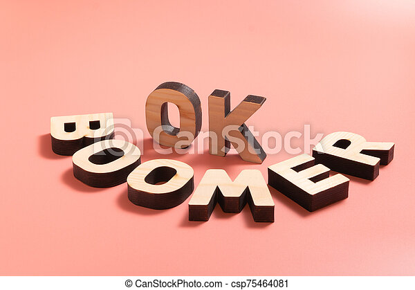 Ok boomer. internet meme popular among young people. wooden words on pink  background. Ok boomer. internet meme popular among