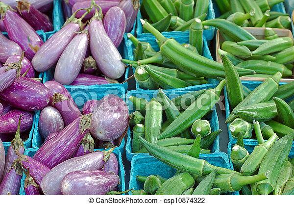 okras and eggplants in buckets in farmer market - csp10874322