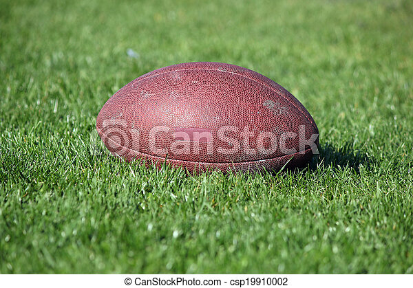 old American football ball on green grass - csp19910002