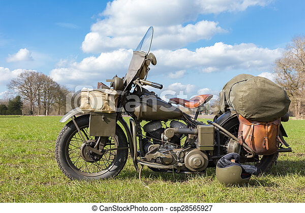 Old american military motorcycle parked on grass - csp28565927
