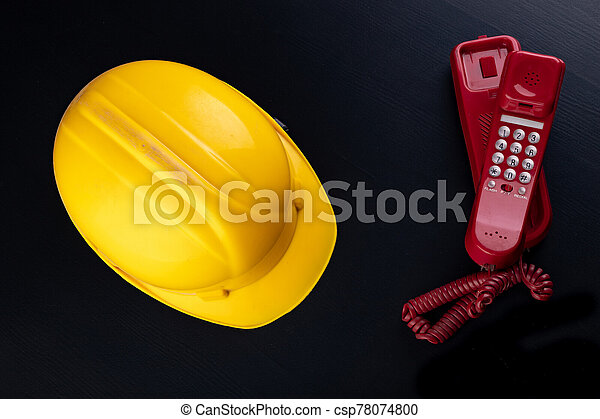 Old analog telephone and helmet on the desk. Accessories for builders in the office. - csp78074800