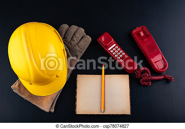 Old analog telephone, helmet and notebook on the desk. Accessories for builders in the office. - csp78074827