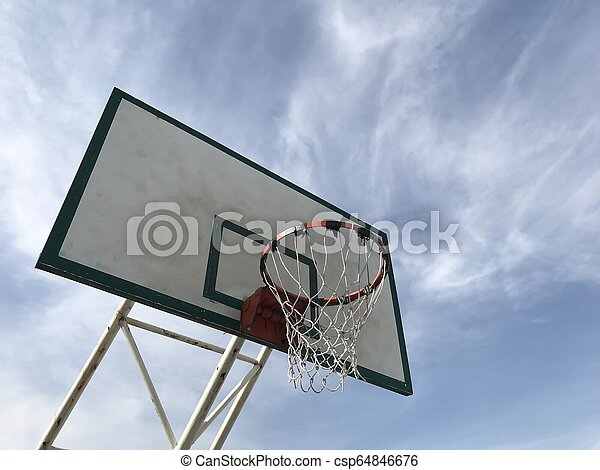 Old basketball hoop under view with blue sky background - csp64846676