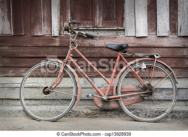 Old bicycle leaning against grungy barn - csp13928939