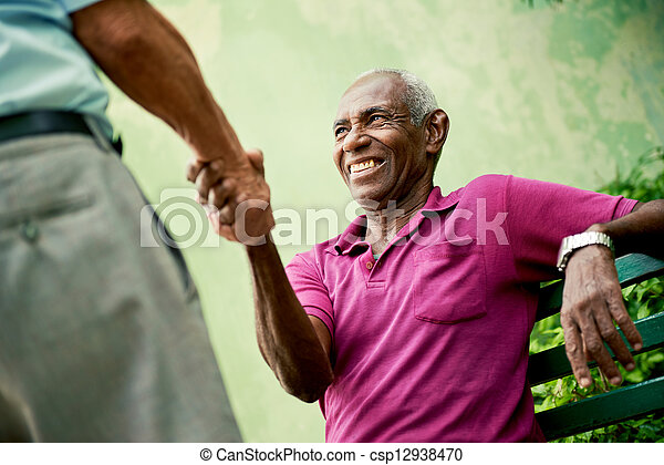 old black and caucasian men meeting and shaking hands in park - csp12938470