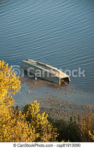 Old boat in the ocean at sunset - csp81913090
