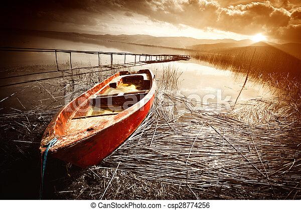 Old Boat on Lake at Sunset - csp28774256