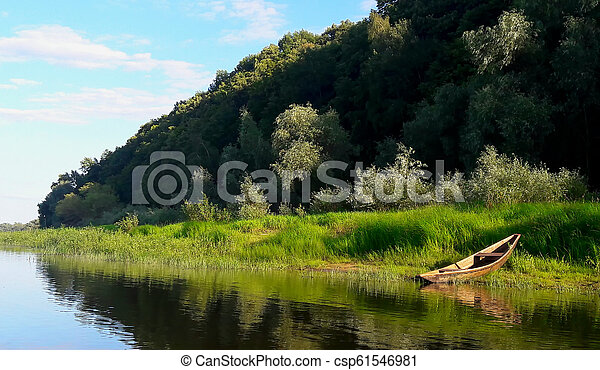 Old boat on the river, green clouds, reflections in the water - csp61546981