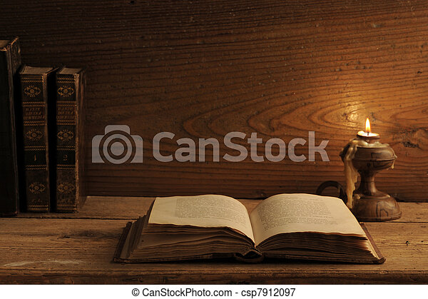 old book on a wooden table by candlelight - csp7912097