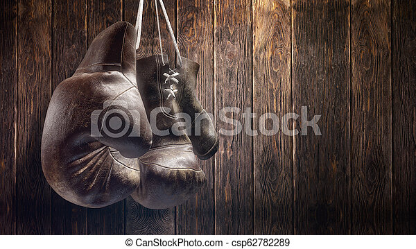 Old boxing gloves hang on nail on wooden wall with copy space for text. High resolution 3d render - csp62782289