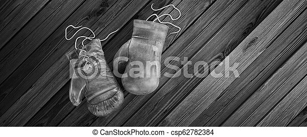 Old boxing gloves lie on the wooden surface with copy space for text. High resolution 3d render - csp62782384