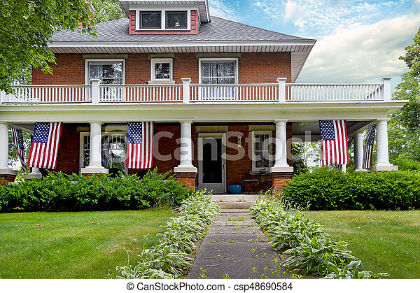 old brick home with American flags - csp48690584