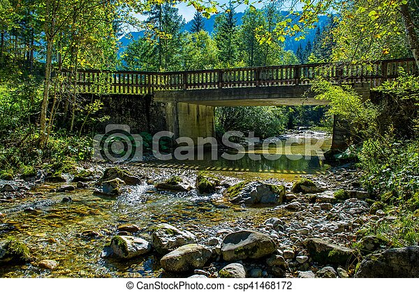 Old Bridge over Sunlit Mountain Creek in Austria - csp41468172