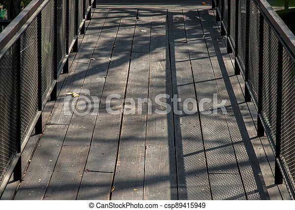 Old brown rustic Wooden walkway with sunlight shine passed through trees and make shadow on the floor. - csp89415949